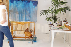 Liz Gray and her dog in front of one of her paintings