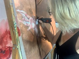 Liz Gray working in her studio on a copper art painting